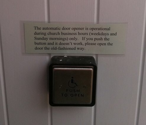 A door opener with a sign over it, sliver button with wheelchair person on it